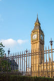 Big Ben tower in London behind fences with blue sky Stock Photography