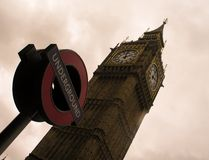 Big Ben tower and the sign of the London Underground against a cloudy sky.  stock photos