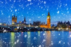 Big Ben and Westminster bridge on a cold winter night. With falling snow, London, United Kingdom Royalty Free Stock Photography