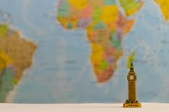 Big ben, a world famous destination. A small model of Big Ben with a world map background Royalty Free Stock Photo