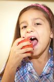 Big bite. Young girl with missing teeth taking a big bite of apple Royalty Free Stock Photos