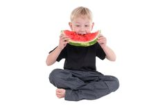 Big bite. Little boy sitting on the floor taking a big bite from a watermelon stock photo