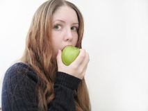 Big bite. Woman taking a big bite out of a green apple royalty free stock photo