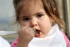 Big Bite. Baby taking a bite of her dinner. (slightly low depth of field ...... strong focus on childs hand and fork royalty free stock photos