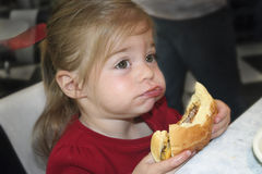 Big Bite. A cute young child takes a big bite out of a hamburger and tries to chew Royalty Free Stock Photo