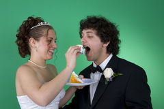 Big Bite of Cake. A couple with their wedding cake stock photo