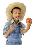 Big Bite Coming. Closeup image of an adorable farm boy preparing to take a big bite out of an apple he holds. On a white background stock image