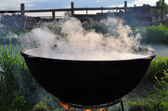 The big black cauldron on the fire with steam. Close-up of sooty cauldron and a pair over them Stock Image
