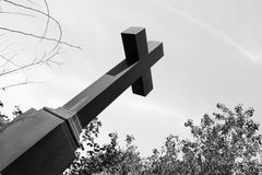 Big black Christian cross. Black and white photography with a cross. High cross on skies and trees. The symbol of the Christian faith Royalty Free Stock Photography