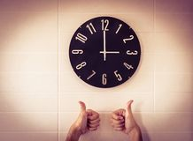 Big black clock on white wall. Time change. DST. Survey of the European Union on time change. Gesture of agreement. Thumbs up of C. A large black clock on a stock photography