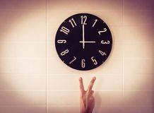 Big black clock on white wall. Time change. DST. Survey of the European Union on time change. Gesture of victory. Caucasian man. royalty free stock photos