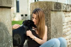 Big black dog spending time with its owner outdoors during summer day. stock photos