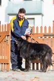 Big black dog welcoming postman at garden gate Royalty Free Stock Image