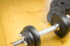 Big black dumbells on wood floor in the huge gym / fitness; spor Stock Images