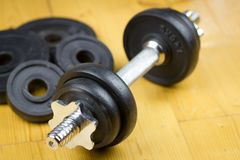 Big black dumbells on wood floor in the huge gym / fitness; spor Stock Photos