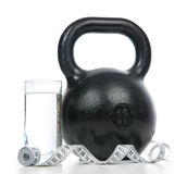 Big black fitness weight with tape measure and glass of drinking Royalty Free Stock Photos