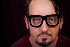 Big Black Glasses. A closeup of a man with a goatee looking at camera with large framed black glasses. Shallow depth of field. Copy Space royalty free stock photography