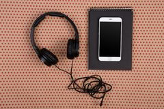 Big black headphones, white smartphone and black notepad on craf. Technology concept - big black headphones, white smartphone and black notepad on craft  paper Royalty Free Stock Photos