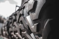 Big black huge big truck, tractor or bulldozer loader tires wheel close-up on stand, shop selling tyres for farming and big vehicl. E moving royalty free stock photography