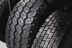 Big black huge big truck, tractor or bulldozer loader tires wheel close-up on stand, shop selling tyres for farming and big vehicl. Es. Lot of pattern tread of royalty free stock image