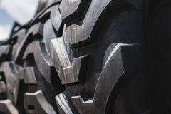 Big black huge big truck, tractor or bulldozer loader tires wheel close-up on stand, shop selling tyres for farming and big vehicl. Es. Lot of pattern tread of stock images