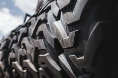Big black huge big truck, tractor or bulldozer loader tires wheel close-up on stand, shop selling tyres for farming and big vehicl. E moving royalty free stock images