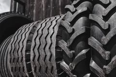 Big black huge big truck, tractor or bulldozer loader tires wheel close-up on stand, shop selling tyres for farming and big vehicl. Es. Lot of pattern tread of stock photos
