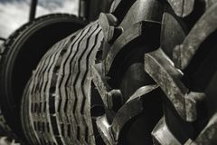 Big black huge big truck, tractor or bulldozer loader tires wheel close-up on stand, shop selling tyres for farming and big vehicl. Es. Lot of pattern tread of royalty free stock photos