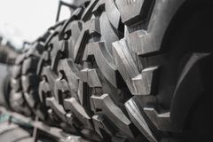Big black huge big truck, tractor or bulldozer loader tires wheel close-up on stand, shop selling tyres for farming and big vehicl. Es. Lot of pattern tread of royalty free stock images