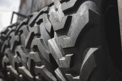 Big black huge big truck, tractor or bulldozer loader tires wheel close-up on stand, shop selling tyres for farming and big vehicl. Es. Lot of pattern tread of stock photo