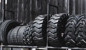 Big black huge big truck, tractor or bulldozer loader tires wheel close-up on stand, shop selling tyres for farming and big vehicl. Es. Lot of pattern tread of royalty free stock photography