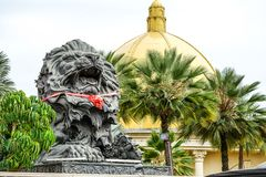 Big black lion statue front of building. Close up big black lion statue with red scarf sitting front of building., Laos stock photography