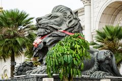 Big black lion statue front of building. Close up big black lion statue with red scarf sitting front of building., Laos royalty free stock photo