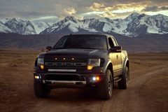 Big black matt American pickup truck Raptor rides on the Kurai steppe at sunset. Glaciers and Altai Mountains in the background. stock images