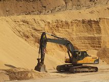Big black orange digger in open sand mine is loading big truck . S Royalty Free Stock Image