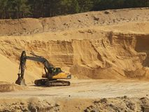 Big black orange digger in open sand mine is waiting for new shift. Royalty Free Stock Photos