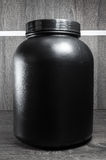 Big black pot of food supplement, no label.  Royalty Free Stock Images