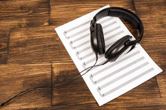 Big black professional headphones lying on the music sheet on the wooden background. Royalty Free Stock Photos