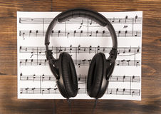 Big black professional headphones lying on the music sheet on the wooden background. Stock Image