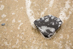 Big Black Rock in Foam Royalty Free Stock Photo
