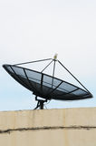 Big Black Satellite Dish on office building. Back satellit set on floor on office building and white blackground Royalty Free Stock Photo