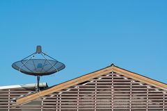 Big Black Satellite Dish on the roof with blue sky. Royalty Free Stock Image