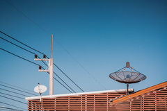Big Black Satellite Dish on the roof with blue sky. Royalty Free Stock Photography