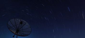 Big Black satellite over spiral star at night Royalty Free Stock Images