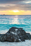 Big black stone on white tropical beach sunset sea Royalty Free Stock Photography