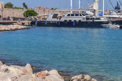 Big black and white docked yacht at Rhodes town marina dock. With blue sea foreground stock images