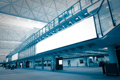 Big Blank Billboard in airport. With moving blurred passenger, blue tune, shot in hong kong, asia royalty free stock photo