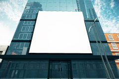 Big blank billboard on glassy business center at sunny day, mock Royalty Free Stock Image