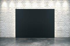 Big blank black canvas on concrete floor. At white brick background Stock Photos