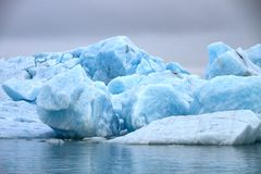 Big blocks of blue ice. Of a glacier floating on the water with a gray sky stock images